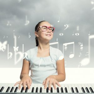 31339878 - pretty school girl in funny glasses playing piano